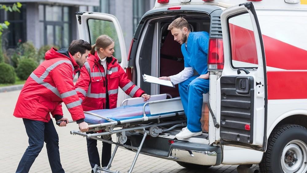 Socorristas retiram maca da ambulância para atender paciente.