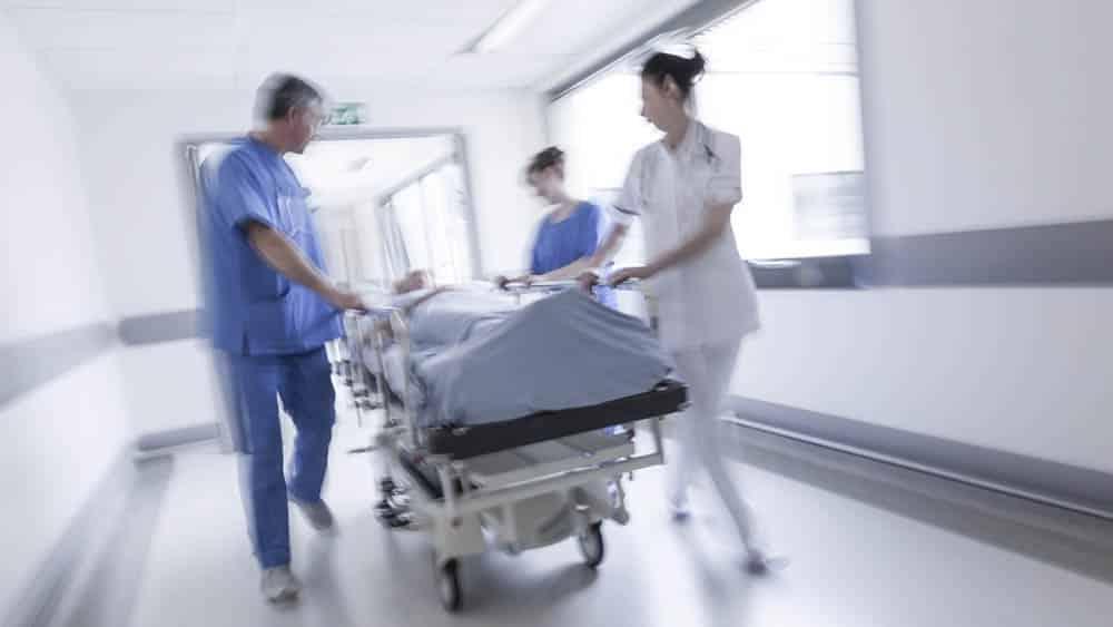 Paciente sendo levado na maca na emergência de hospital. SUS é o maior sistema público de saúde do mundo, mas tem gargalos