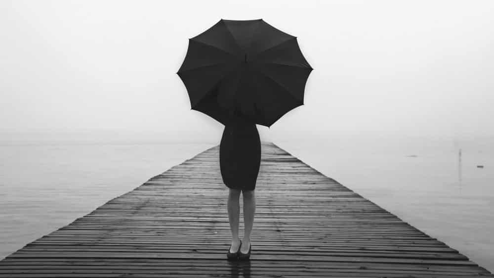 mulher em pé em uma ponte, segurando um guarda-chuva. Muitas vezes, a angústia não tem causa aparente