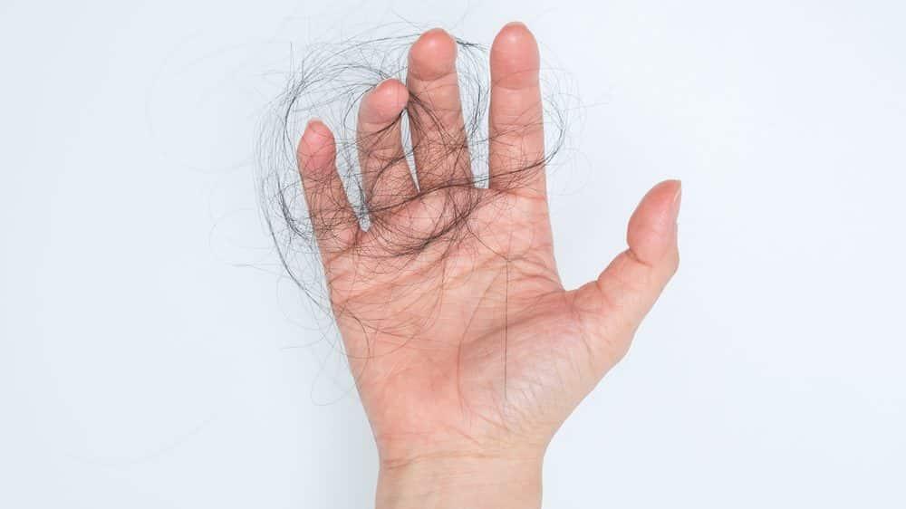 mão segurando tufos de cabelos