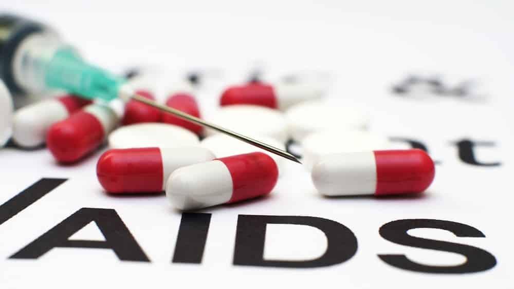 comprimidos sobre cartaz escrito 'aids'. Brasil corre o risco de ver a volta do HIV