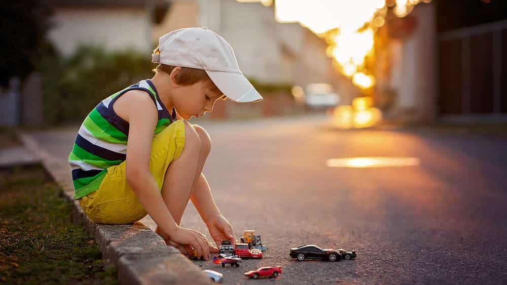 menino brinca com carrinhos no meio fio. Felicidade plena, só experimentamos na infância