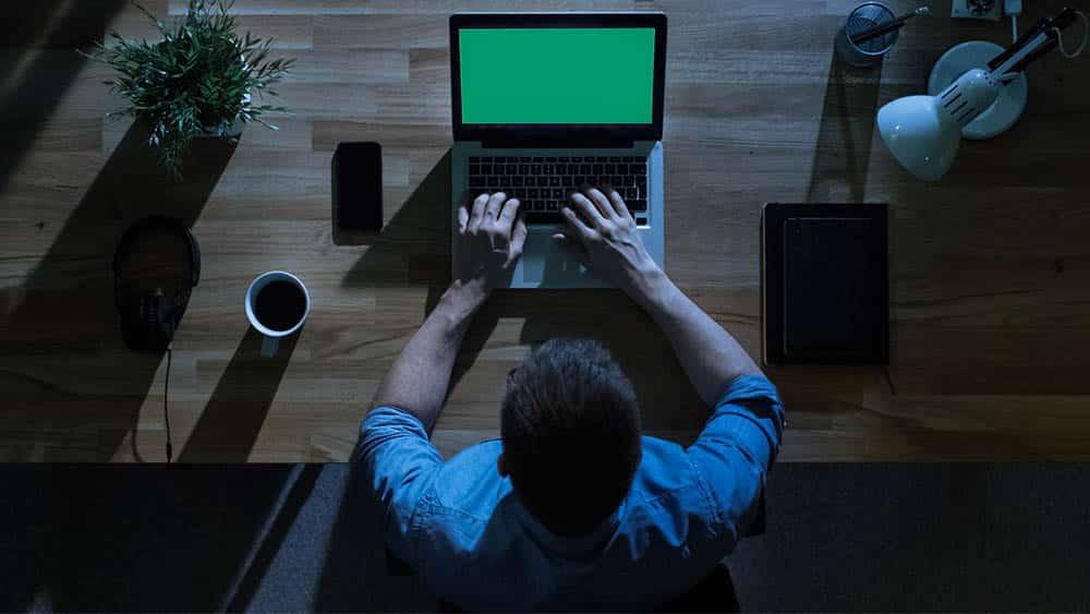 Vista de cima de um homem trabalhando no computador no escuro. Avanços tecnológicos aumentam a carga de trabalho