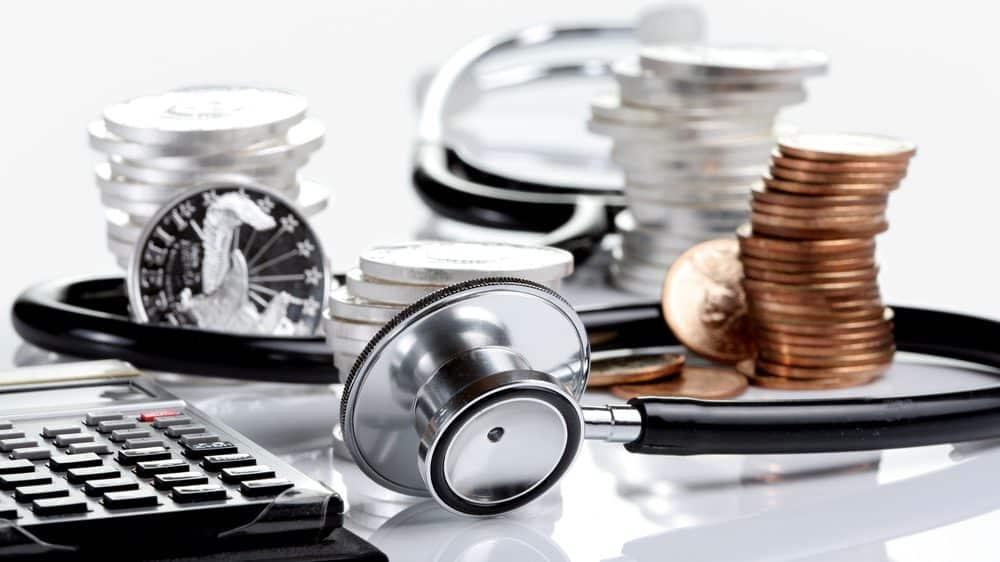moedas e estetoscópico relacionando investimento em saúde