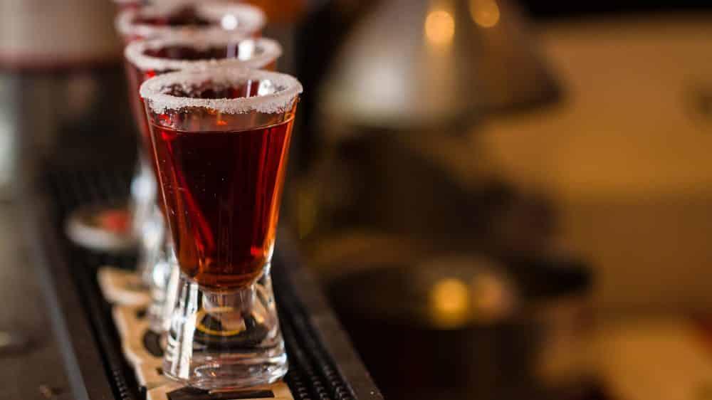 imagem de copos pequenos cheios de bebida alcoólica. Álcool e demência podem estar relacionados