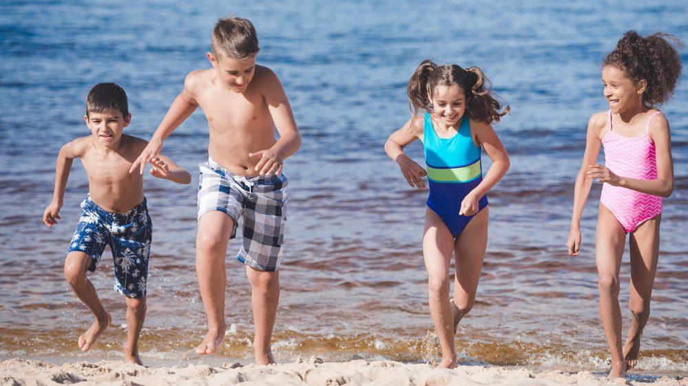 Crianças brincando na beira do mar, expostas ao sol.