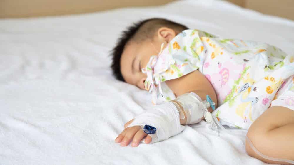 Criança com meningite dormindo em cama hospitalar enquanto toma soro.