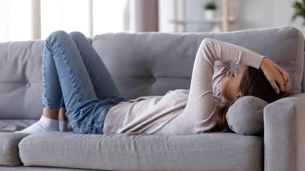 mulher deitada no sofá. síndrome da fadiga crônica causa cansaço excessivo