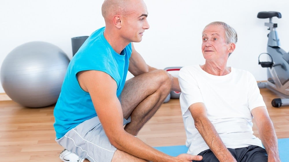 idoso praticando exercícios com acompanhamento de treinador.