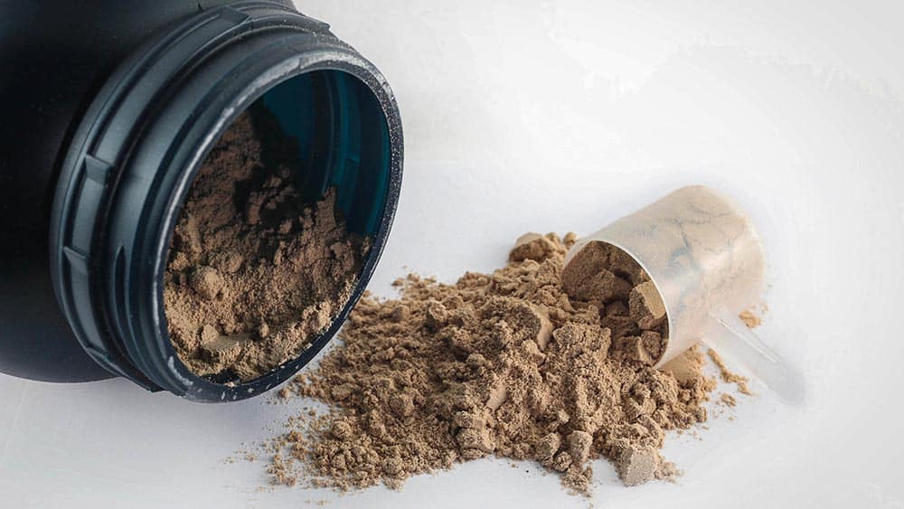 Pote de suplemento alimentar whey protein caído e ao lado colher de medida.