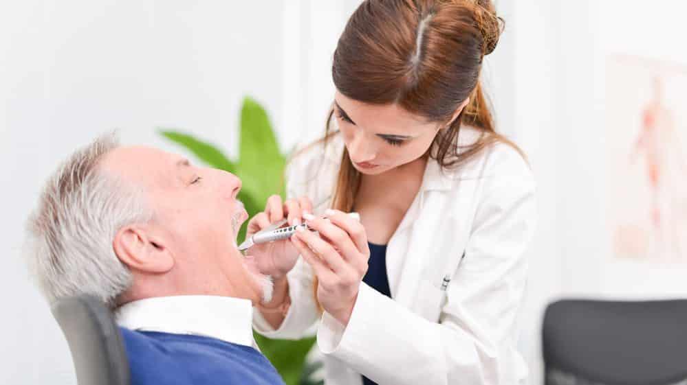 médica examina a cavidade oral de paciente. câncer de garganta atinge mais homens