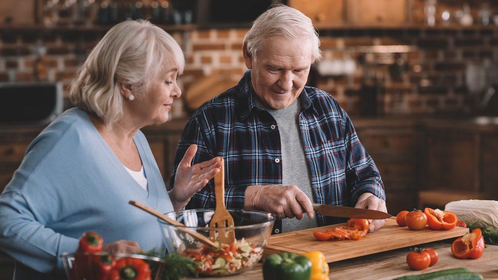 casal de idosos cozinhando alimentos saudáveis. Estilo de vida saudável diminui o risco de demência