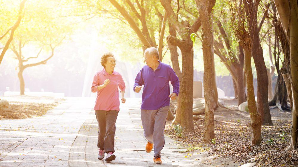 casal de idosos praticando corrida em parque. exercícios físicos regulares auxiliam na prevenção do Alzheimer