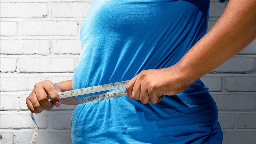 Homem obeso de perfil medindo circunferência abdominal.