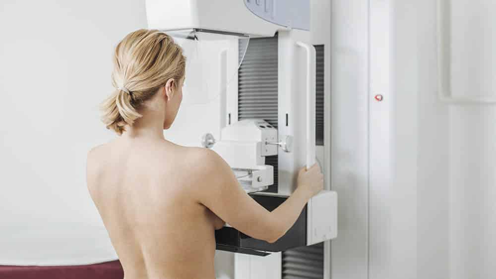 Mulher de costas fazendo mamografia.