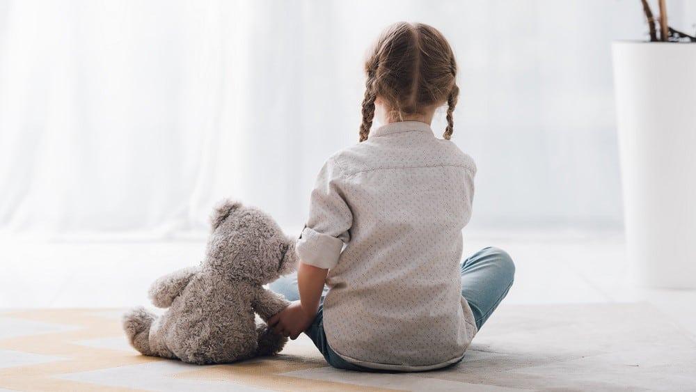 Menina de costas sentada no chão com urso de pelúcia ao lado.