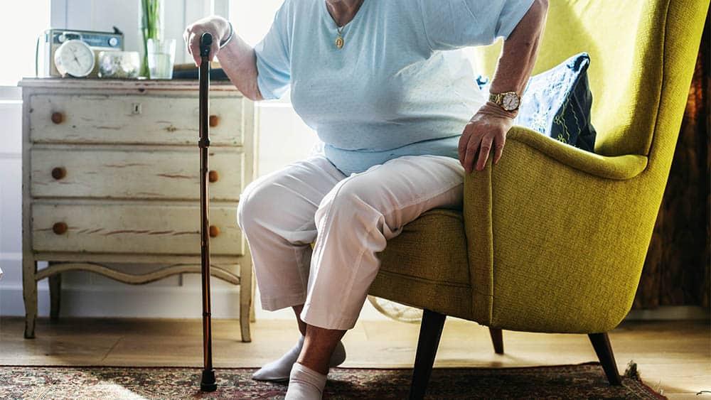 Idosa com bengala levantando de cadeira. Há associação entre sarcopenia e mortalidade