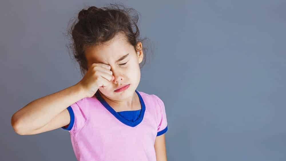 Menina esfregando o olho direito em sial de cansaço.