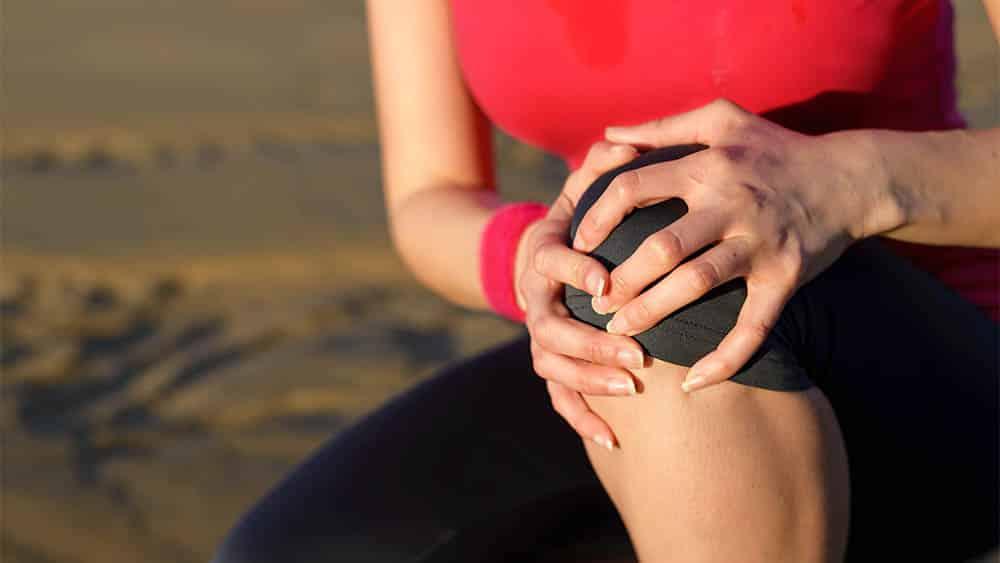 Corredora agachada com a mão no joelho em sinal de dor