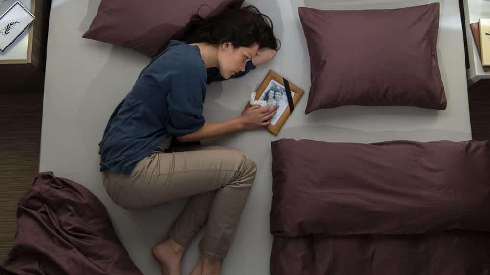 mulher enfrenta luto de ente querido deitada na cama com porta-retratos ao lado