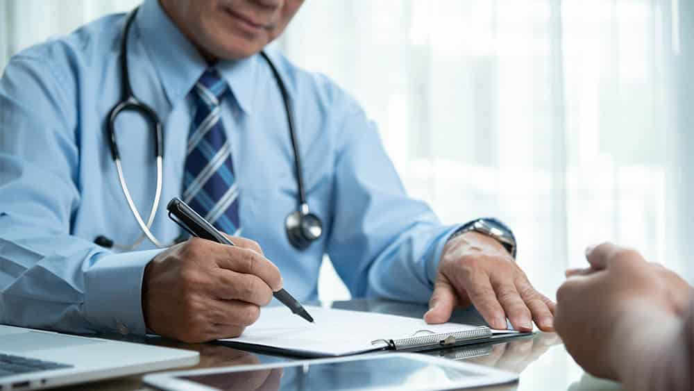 Médico em consulta com paciente escrevendo prescrição.