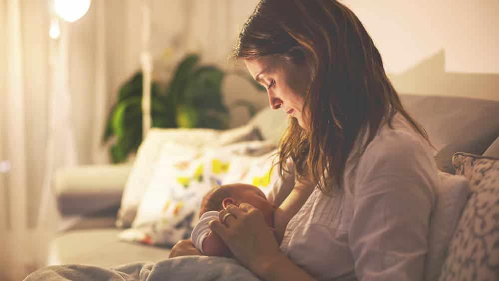 Mãe amamentando bebê sentada em sofá com luz suave. sempre há dúvidas sobre amamentação