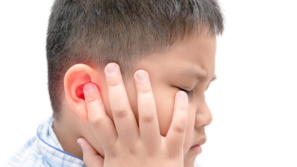 Menino tenso, com mão na orelha em sinal de dor de ouvido