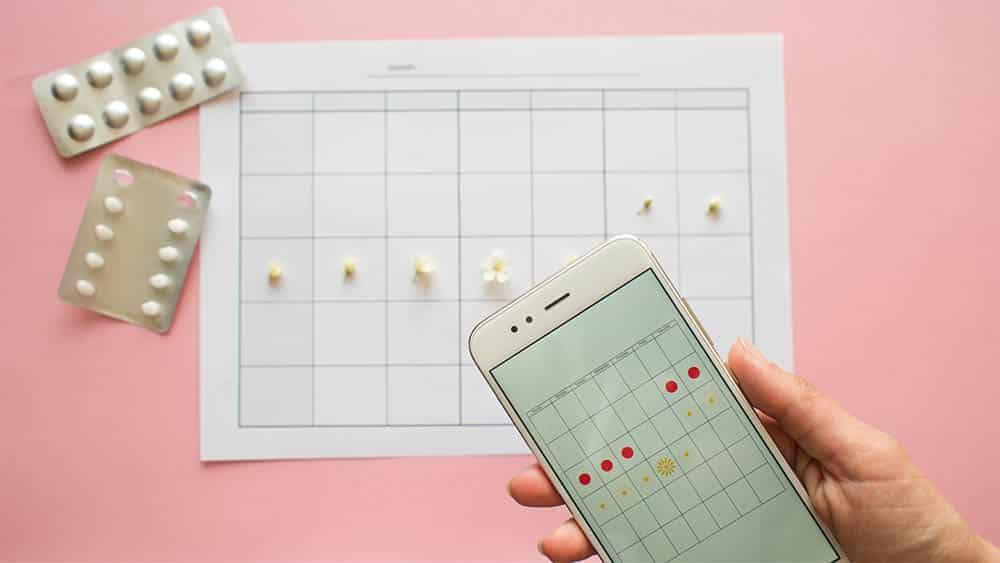 Vista de cima de calendário com dias marcados, cartelas de anticoncepcional e, em primeiro plano, mão feminina segurando celular com aplicativo de ciclo menstrual na tela.