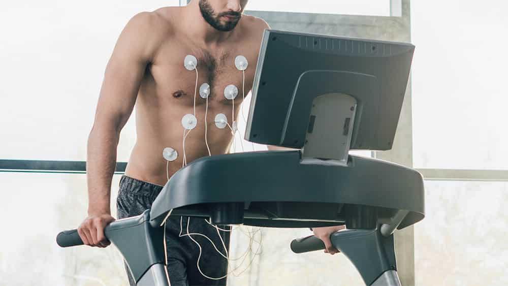 Homem com eletrodos no tórax fazendo teste ergométrico em esteira.
