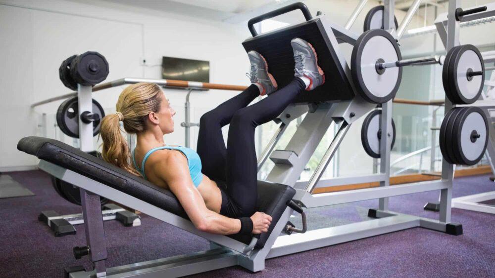 Mulher na academia fazendo leg press.