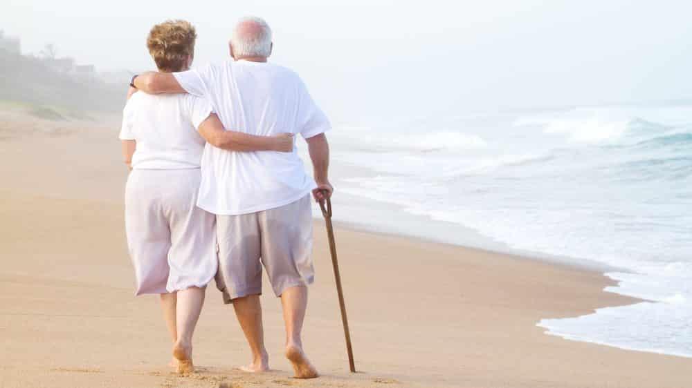 casal de idosos andando na praia. Envelhecimento e saúde podem andar juntos