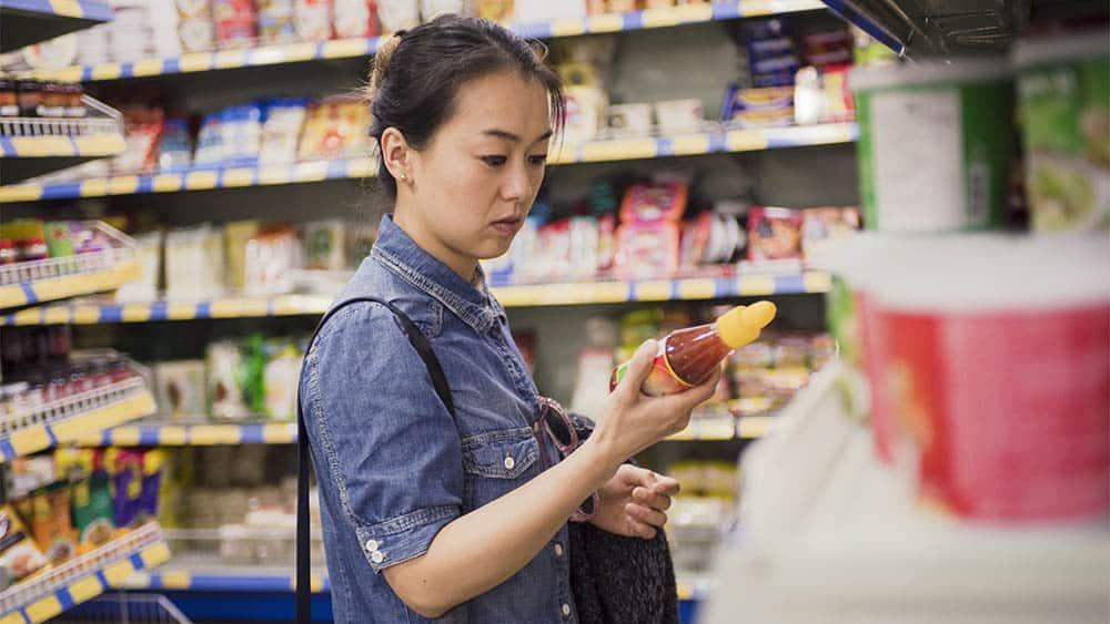 Mulher em supermercado segurando produto e olhando rótulos de alimentos.