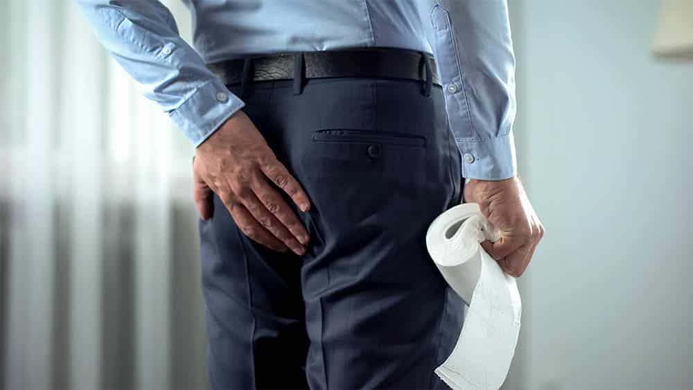 Executivo de costas com mão nas nádegas e segurando rolo de papel higiênico, em sinal de fissura anal