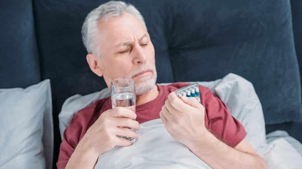 homem toma remédio na cama. hora de tomar medicamento interfere no tratamento da hipertensão