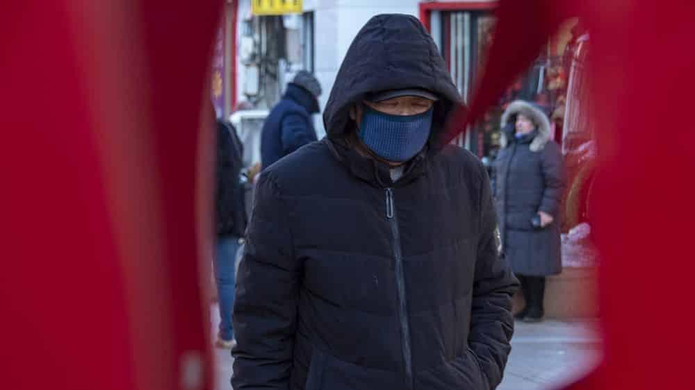 homem usa máscara para se proteger do novo coronavírus em rua da China