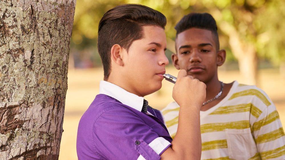 adolescente fuma cigarro eletrônico ao lado de amigo. Uso de cigarro eletrônico na adolescência traz sérios riscos à saúde