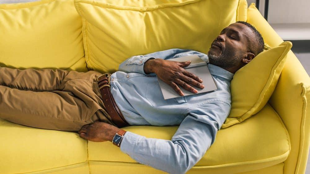 homem dormindo no sofá, com livro aberto sobre o peito. estudo mostra associação entre sono e avc