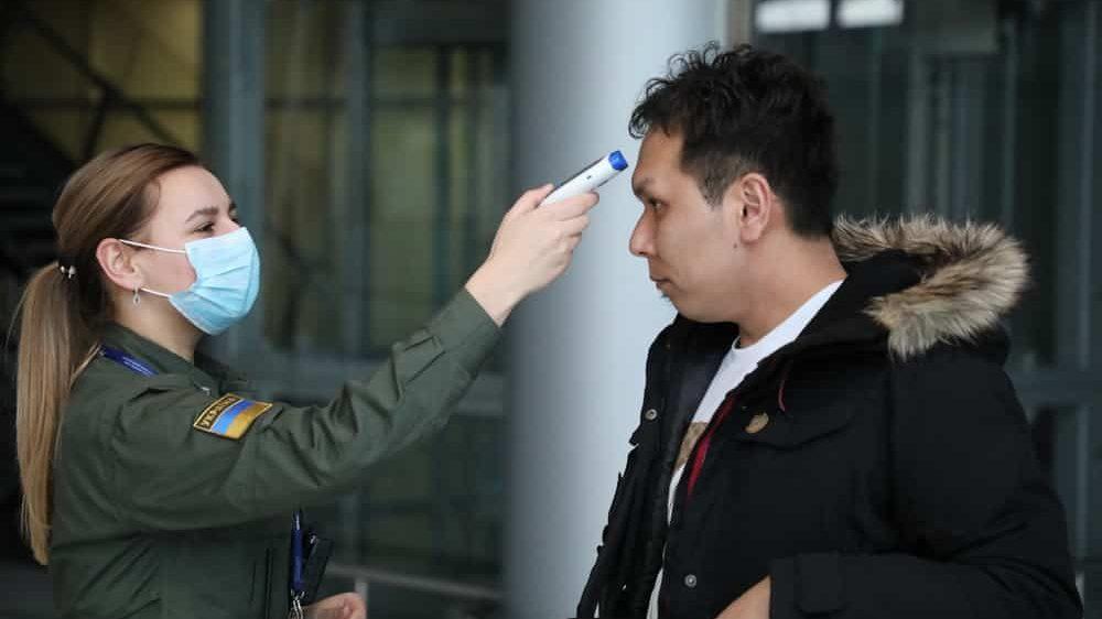funcionária mede temperatura na testa de passageiro para realizar triagem de covid-19 nos aeroportos