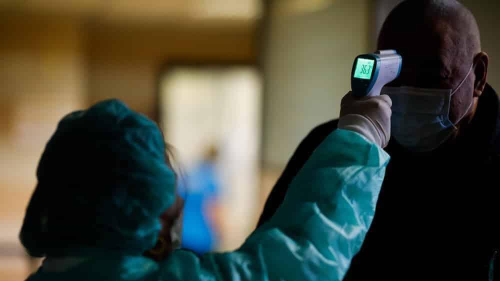 enfermeira mede temperatura na testa de suposto paciente com novo coronavírus