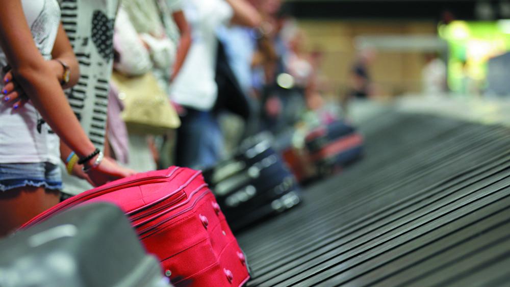 Pessoas chegando de viagem internacional aguardando sua bagagem. Elas devem ficar atentas aos sintomas que podem indicar infecção pelo novo coronavírus