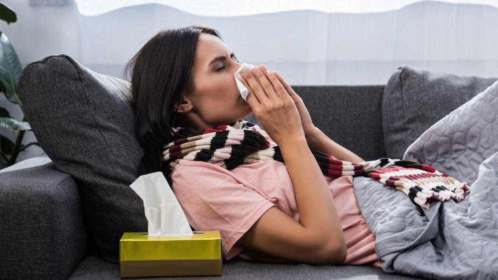 Mulher deitada assoando nariz com lenço.