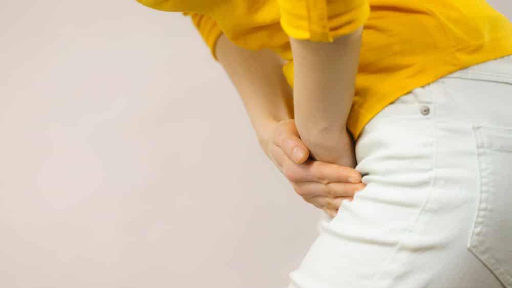 Mulher com blusa amarela sofre de dor causada por infecção urinária.