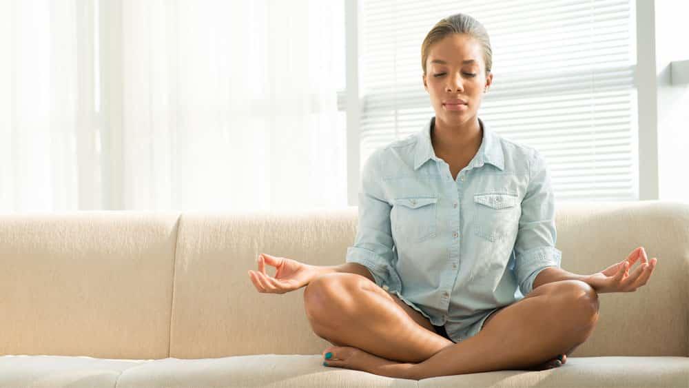 Mulher negra pratica meditação em casa, uma das formas de reduzir os efeitos da quarentena por conta do novo coronavírus.