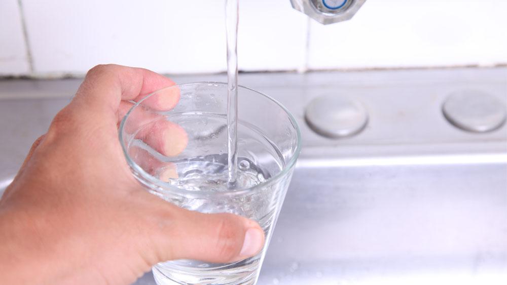 Homem segura copo para tomar água em casa, durante a quarentena.