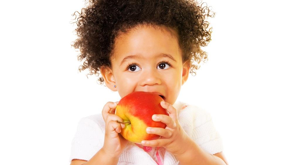 menina pequena morde maça. veja dicas para cuidar da alimentação das crianças na quarentena
