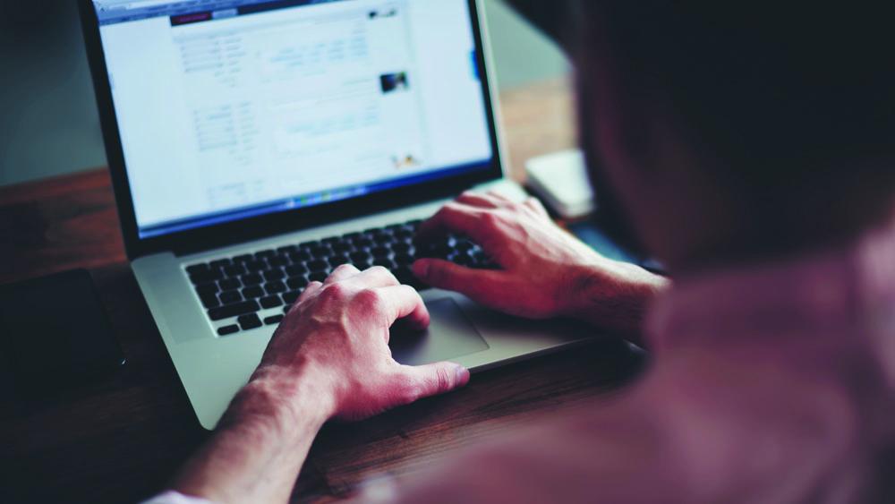 Homem trabalhando em casa com notebook. Organizar a estação de trabalho é uma das dicas para lidar com o home office na quarentena.