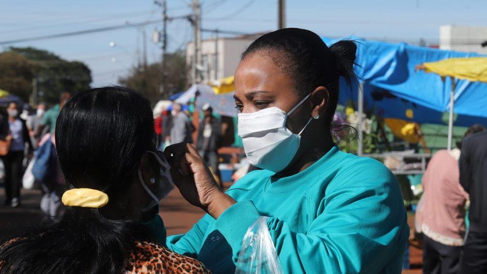 mulher de máscara ajusta a máscara de outra mulher em feira livre no Paraná. A epidemia brasileira atinge todos os estados