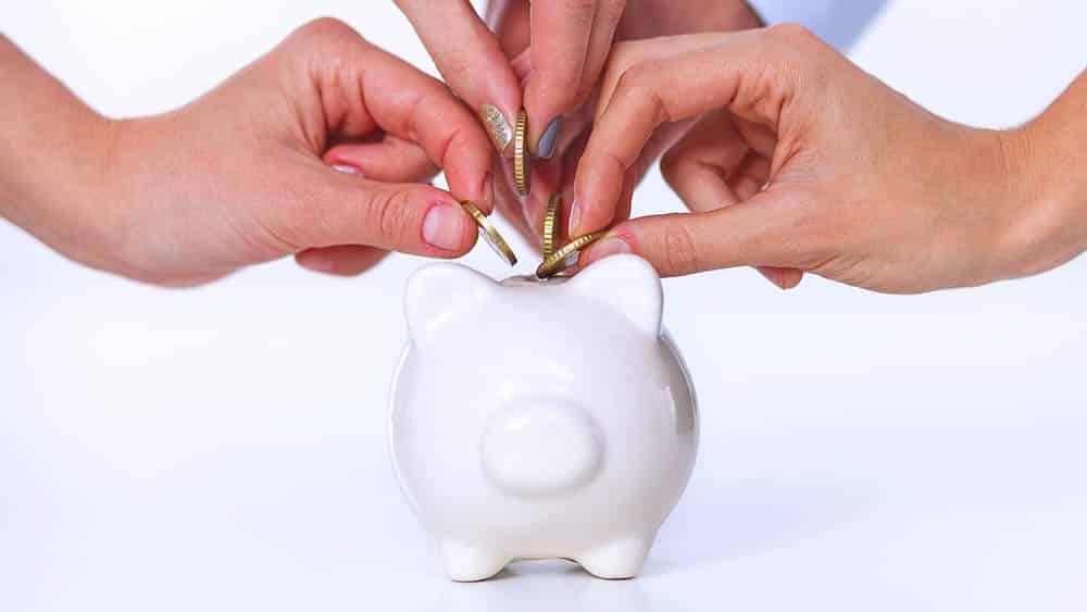 Várias mãos colocando moedas em um cofre porquinho.