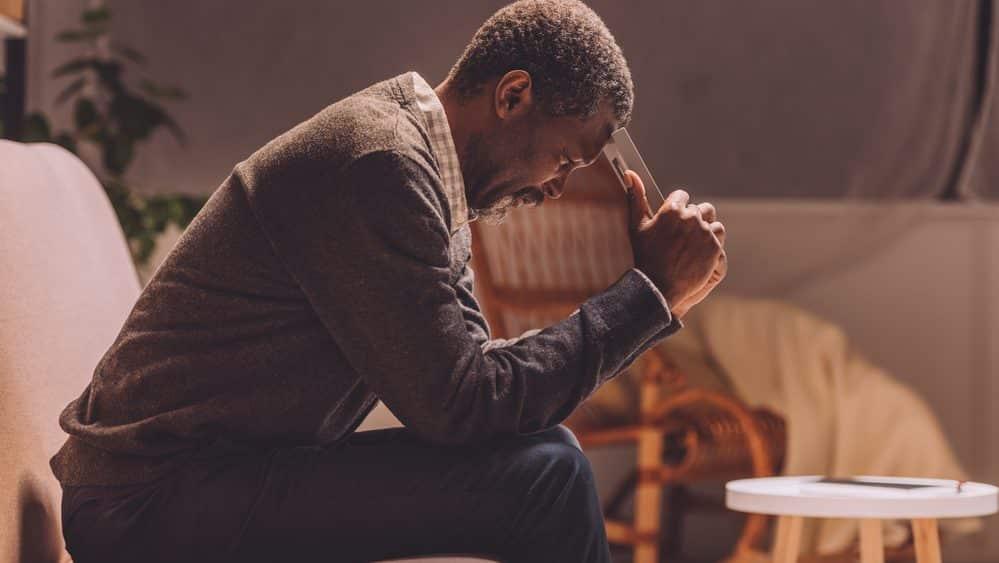 homem sentado, com a cabeça apoiada nas mãos. Isolamento social pode agravar depressão