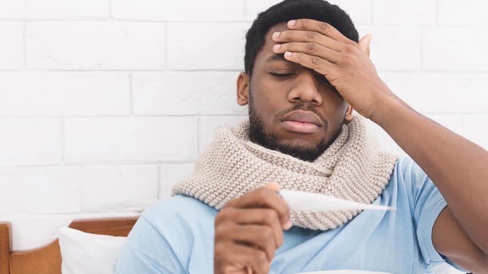 homem doente na cama olha termômetro. febre é um dos sintomas da covid-19